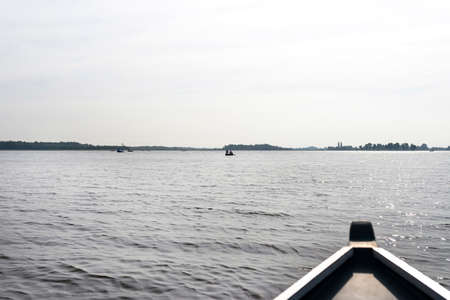 Picture taken from a wooden boat, visible people floating on the boats, the bow of the boat is blurry.