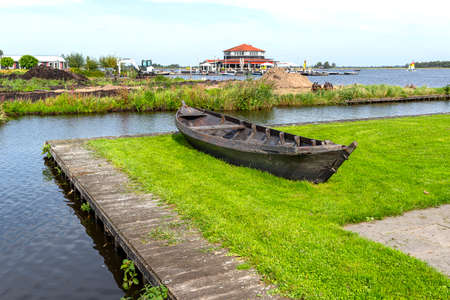 An old wooden boat standing on the shore on the grass, in the background a restaurant and a lake. Archivio Fotografico