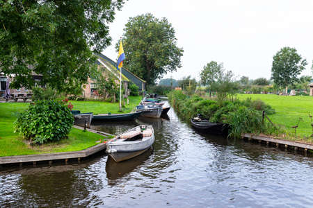 Metal and wooden boats that are standing moored in the channel, visible trees and buildings.