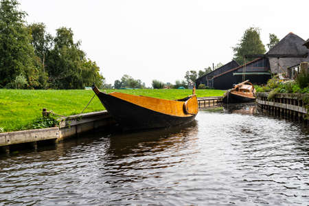A wooden boat is moored in a canal by the shore, visible trees and buildings.
