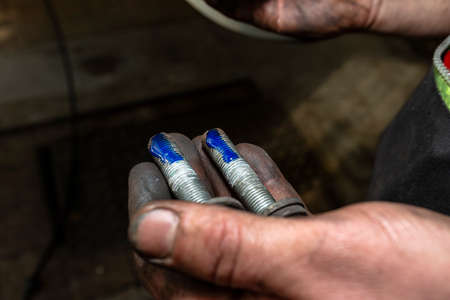 Car mechanic applies a layer of blue thread glue to the screw in his hand.