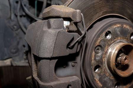 Old front brake disc with caliper and brake pads in the car, on a car lift in a workshop, close-up of a brake caliper.