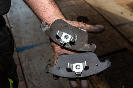 A car mechanic holds in a dirty, open hand a new and old brake pad, visible rear part of the pads.
