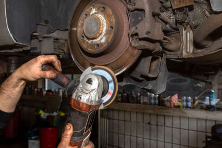 A mechanic grinds, with an angle grinder, the edge of an old rear brake disc in a car, regeneration of the brake system. Banque d'images - 157788552