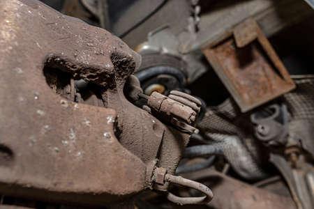 Old brake hose system, mounted to the car, close-up on the handbrake tensioning spring.