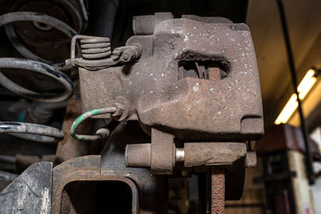 Old brake hose system, mounted to the car, close-up on the spring that tensions the handbrake and the brake caliper. Banque d'images