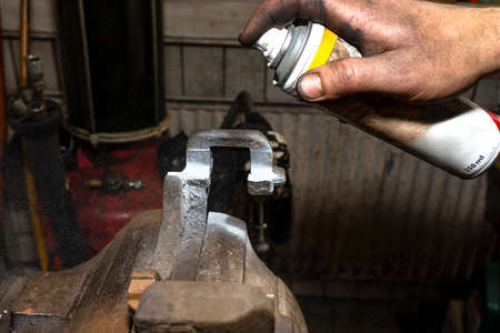 The mechanic lubricates the brake caliper in a table vise with ceramic grease. Zdjęcie Seryjne