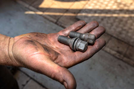 A car mechanic holds in his open, dirty hand metal screws for screwing aluminum and steel rims. 스톡 콘텐츠