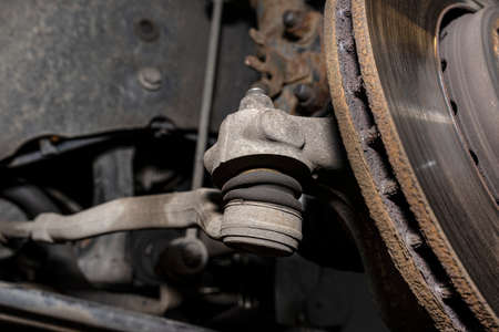 The end of the tie rod ends with a rubber connector, the brake disc is visible.