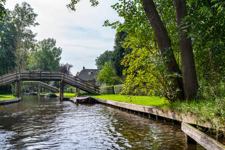 A canal flowing between buildings in a famous village in the Netherlands, visible trees and flowers in the gardens. 免版税图像