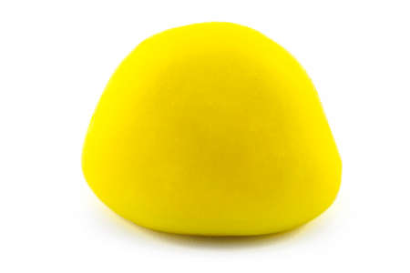 A macro shot of a hard coated yellow candy, isolated on a white background. Imagens