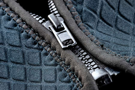 Macro shot of a half-closed, plastic zipper in a modern blue garment.