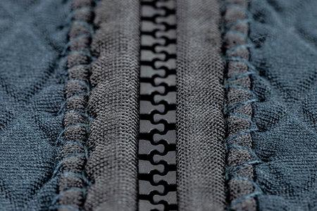 A macro shot of a closed, plastic zipper in a modern blue garment.