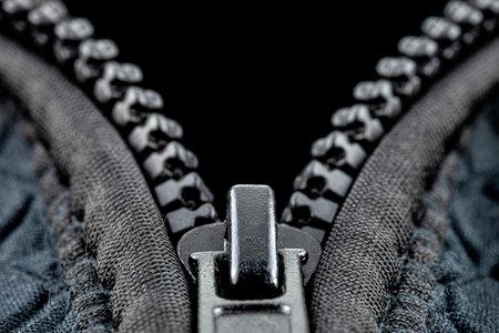 A macro shot of a open, plastic zipper in a modern blue garment.