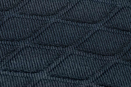 Background made from a macro of real material in dark blue, diamond shapes.