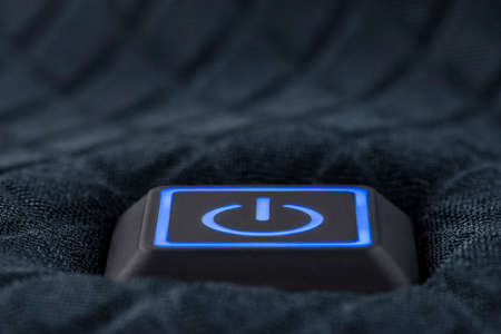 Macro shot of a plastic button with a blue power symbol, sewn into modern clothing.