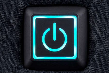 Macro shot of a plastic button with a turquoise power symbol, sewn into modern clothing, top view. Standard-Bild