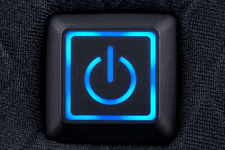 Macro shot of a plastic button with a blue power symbol, sewn into modern clothing, top view. Standard-Bild