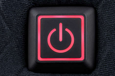 Macro shot of a plastic button with a red power symbol, sewn into modern clothing, top view.