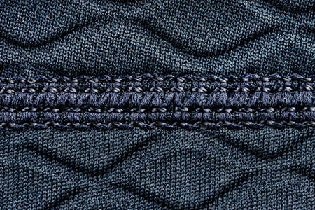 Macro background made of a seam on a fabric in navy blue color, rhomboid shapes.