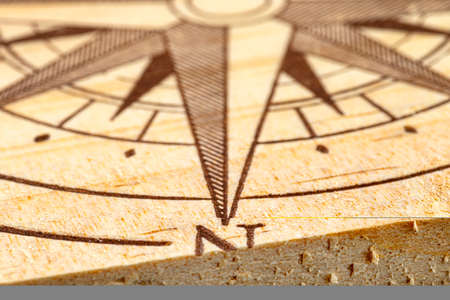 Macro shot of a compass painted on a wooden plank, small depth of field, close-up to the north direction.