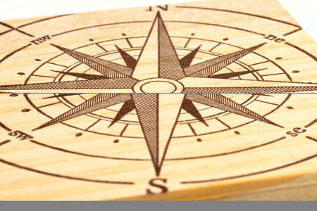 Macro shot of a compass painted on a wooden plank, small depth of field.