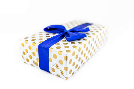 A gift wrapped in white paper with gold circles wrapped in a blue ribbon tied in a bow, isolated on a white background, shallow depth of field.