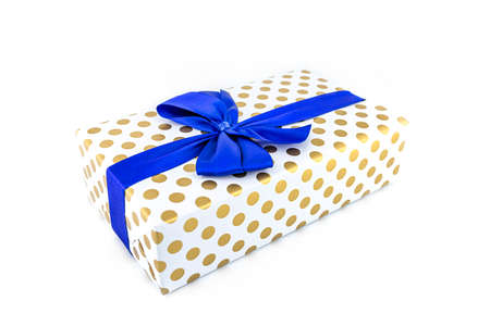 A gift wrapped in white paper with gold circles wrapped in a blue ribbon tied in a bow, isolated on a white background.