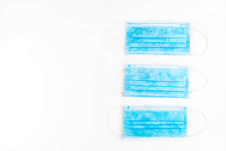 Three blue surgical masks for personal protection against the virus, isolated on a white background, top view.