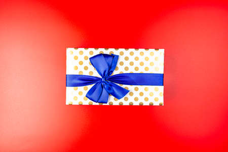 A gift wrapped in white paper with gold circles wrapped in a blue ribbon tied in a bow, isolated on a red background, top view. Standard-Bild