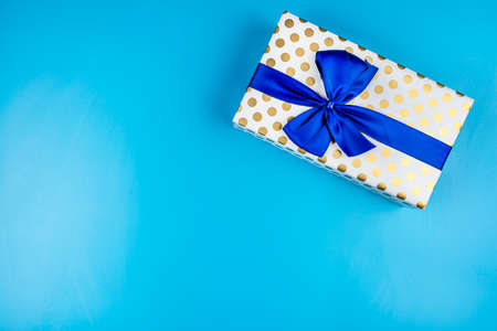 A gift wrapped in white paper with gold circles wrapped in a blue ribbon tied in a bow, isolated on a blue background, top view. Standard-Bild