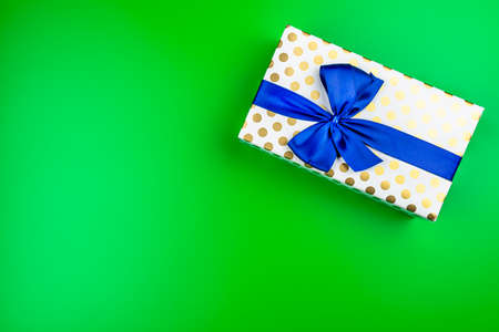 A gift wrapped in white paper with gold circles wrapped in a blue ribbon tied in a bow, isolated on a green background, top view.