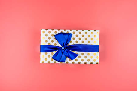 A gift wrapped in white paper with gold circles wrapped in a blue ribbon tied in a bow, isolated on a pink background, top view.
