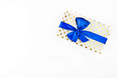 A gift wrapped in white paper with gold circles wrapped in a blue ribbon tied in a bow, isolated on a white background, top view.
