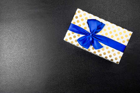 A gift wrapped in white paper with gold circles wrapped in a blue ribbon tied in a bow, isolated on a black background, top view.