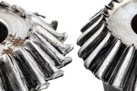 Macro shot of a two damaged bevel gears with beveled teeth, isolated on a white background.