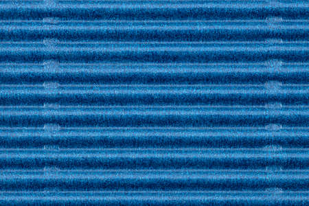 Background made of blue corrugated cardboard with horizontal stripes, view from above.