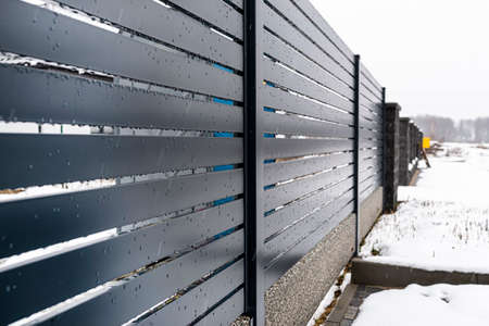 Modern anthracite panel fencing, with a visible fence foundation connector, it rains in winter, in the background there is snow lying on the ground.