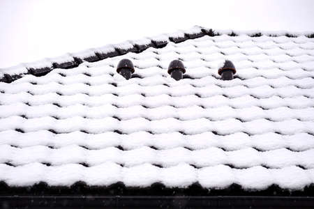 The roof of a single-family house is covered with snow against a cloudy sky, visible ceramic ventilation fireplace on the roof and falling snow.