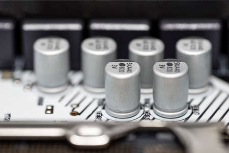 A macro shot of six capacitors in a metal housing, soldered to the motherboard of a desktop computer.