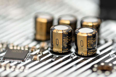 A macro shot of five capacitors in a metal housing, soldered to the motherboard of a desktop computer.