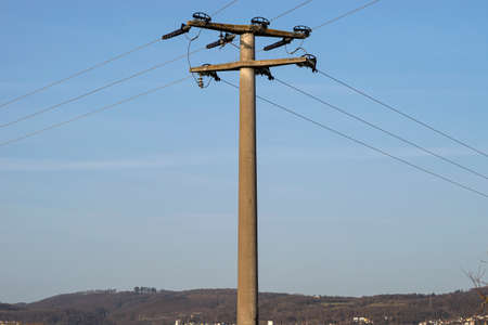 Concrete electric pole with ceramic insulators and voltage lines, in background blue sky with blue sky.