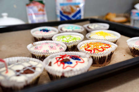 Chocolate brown muffins wrapped in white paper and covered with white frosting with colorful decorations, baked in the oven, lying on baking paper.