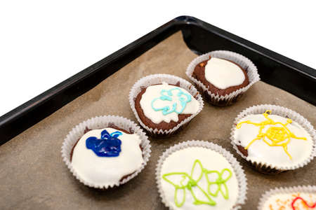 Chocolate brown muffins wrapped in white paper and covered with white frosting with colorful decorations, baked in the oven