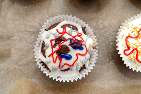 Chocolate brown muffins wrapped in white paper and covered with white frosting with colorful decorations, baked in the oven, lying on baking paper, top view.