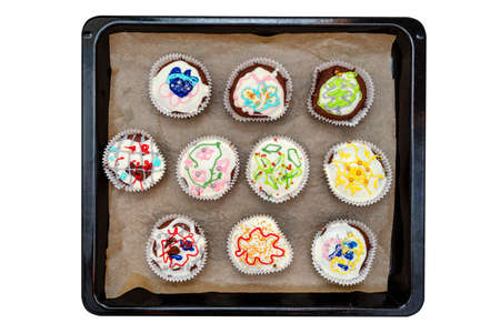 Chocolate brown muffins wrapped in white paper and covered with white frosting with colorful decorations, isolated on white lying on baking paper, top view. Zdjęcie Seryjne