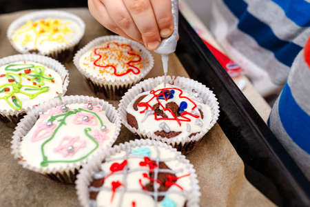 A child squeezes colored frosting from a tube onto chocolate brown cupcakes covered with white frosting with colorful decorations.