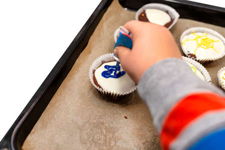A child squeezes colored frosting from a tube onto chocolate brown cupcakes covered with white frosting with colorful decorations, isolated on white.