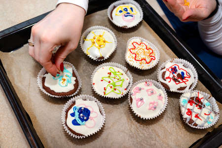 A woman squeezes colored frosting from a tube onto chocolate brown cupcakes covered with white frosting with colorful decorations, top view.
