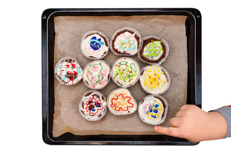 A child squeezes colored frosting from a tube onto chocolate brown cupcakes covered with white frosting with colorful decorations, isolated on white, top view.